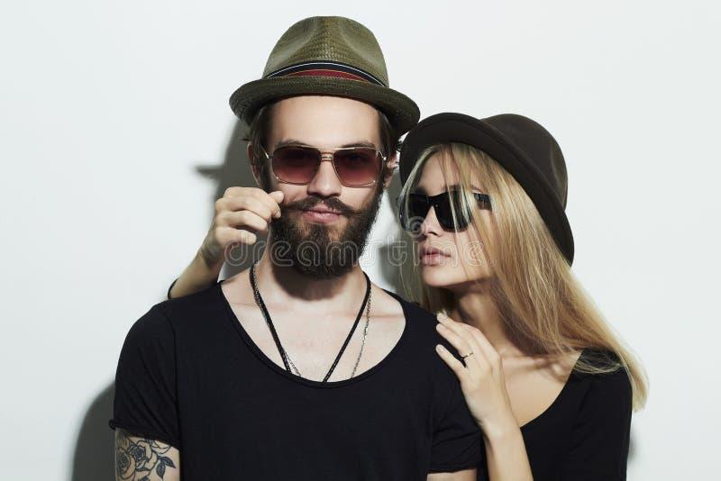 Härliga par i hatten som tillsammans bär moderiktiga exponeringsglas Hipsterpojke och flicka royaltyfri fotografi