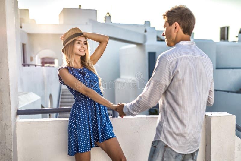 Härliga par som flörtar hållhänder på det första datumet, möte Sommar på den utomhus- solnedgången royaltyfri foto