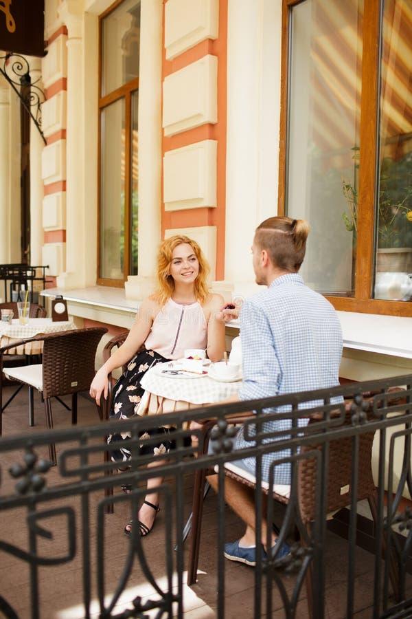 Härliga par som har kaffe på ett datum och att ha gyckel tillsammans arkivfoto