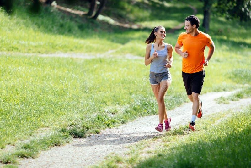 Härliga par som joggar i natur arkivbild