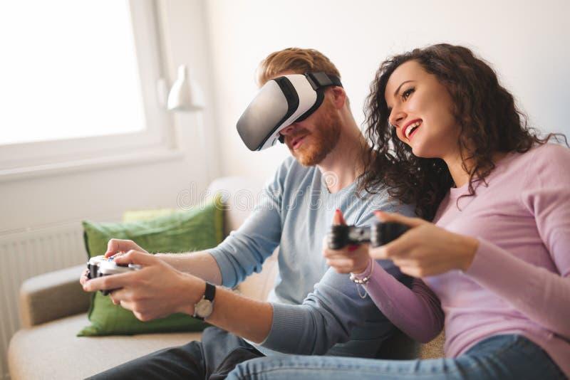 Härliga par som spelar videospel på konsolen royaltyfri fotografi