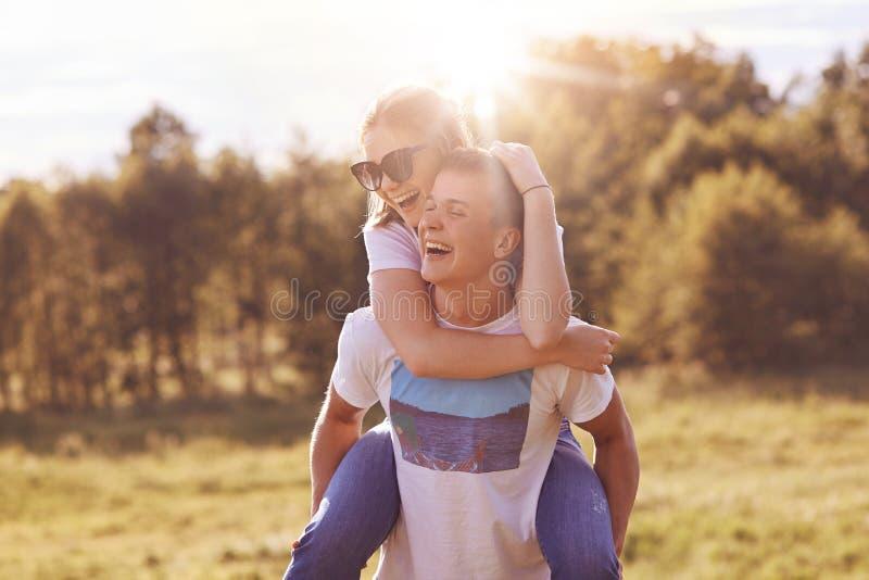Härliga par står utomhus, har gyckel, pojke ger sig på ryggen till hans bästa kvinnliga vän, har positiva leenden på framsidor, p royaltyfria bilder