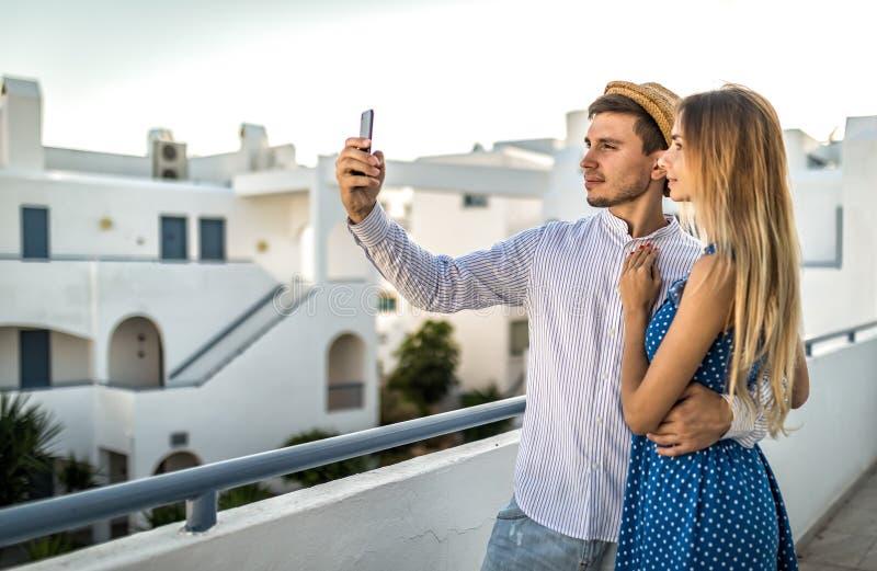Härliga par tar selfies i Santorini Grekland sommar, utomhus- eller utvändigt fotografering för bildbyråer