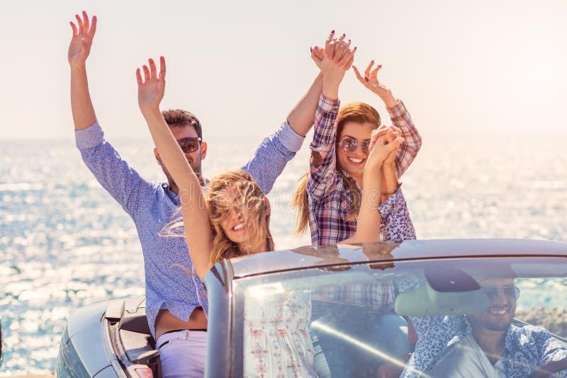 Härliga partivänflickor som dansar i en bil på den lyckliga stranden royaltyfri bild