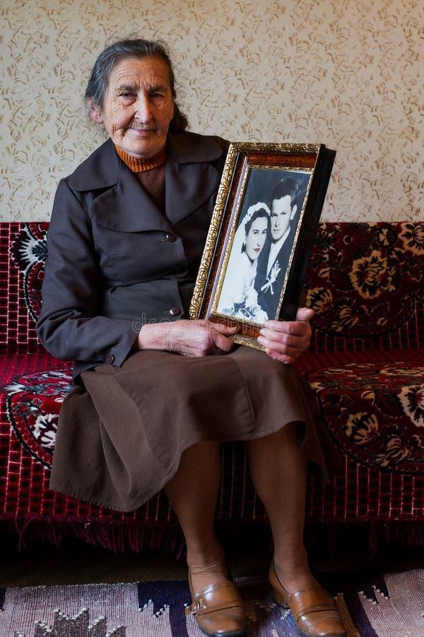 Härliga 80 plus den åriga höga kvinnan som rymmer hennes bröllopfotografi Förälskelseför evigtbegrepp fotografering för bildbyråer