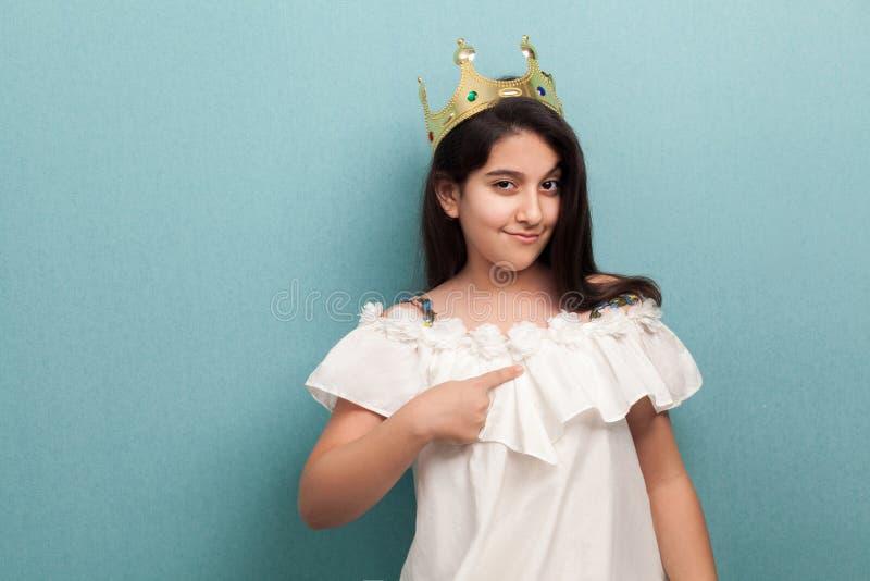 H?rliga prinsessakl?der f?r ung arrogans i den vita kl?nningen och guld- diademen som st?r och pekar fingret till henne och att s arkivfoton