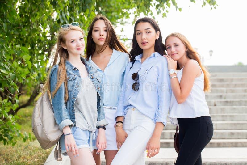 Härliga roliga fyra flickvänner jublar och ler på kameran i parkera i sommaren arkivbilder