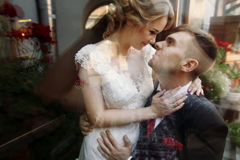 Härliga romantiska nygift personpar som kramar nära blommabuketter arkivbilder