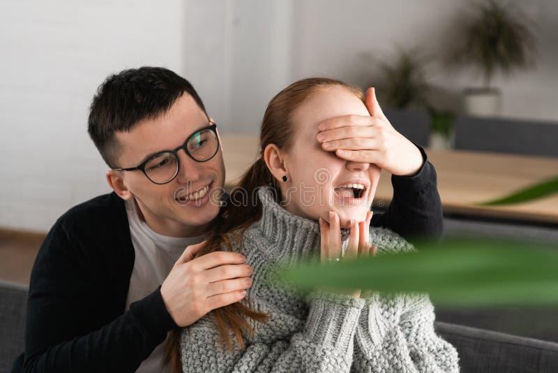 Härliga romantiska par för överraskning i kafé Mannen täcker hans flickväns ögon medan henne som väntar på en överraskning royaltyfri bild