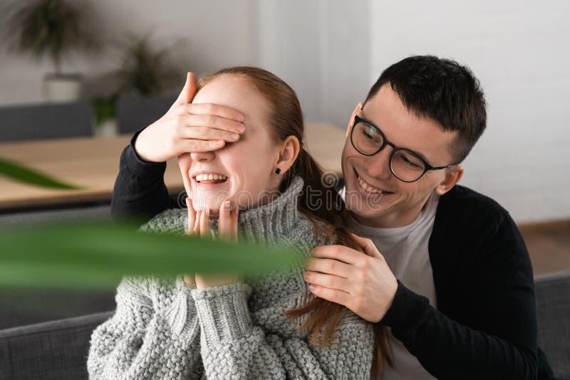 Härliga romantiska par för överraskning i kafé Mannen täcker hans flickväns ögon medan henne som väntar på en överraskning arkivfoton
