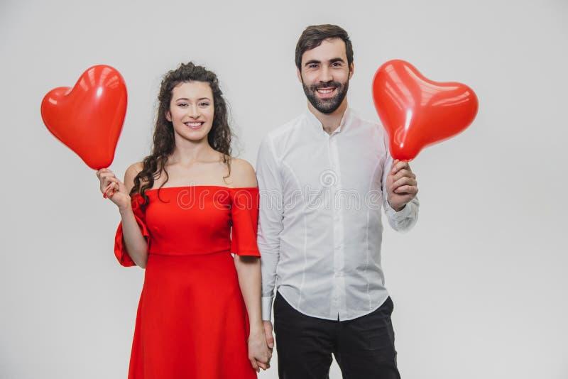 Härliga romantiska par som isoleras på vit bakgrund En attraktiv ung kvinna och härliga händer lyfter ballonger in royaltyfri foto