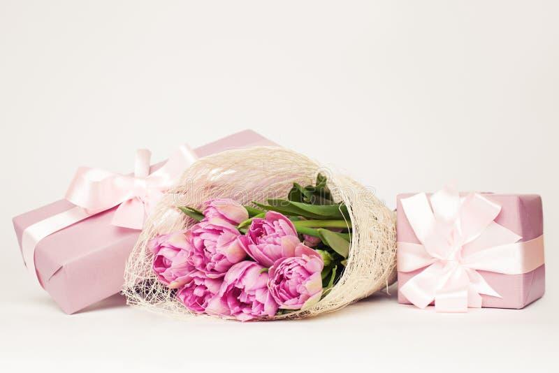 Härliga rosa färgblommor och gåvaask på vit royaltyfri bild