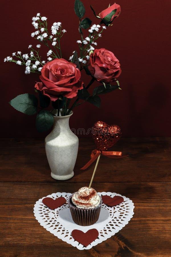 Härliga rosa rosor i en vas som betonades med brudslöjablommor, hjärta formade vit dollie med en dekorerad koppkaka med honom arkivbilder