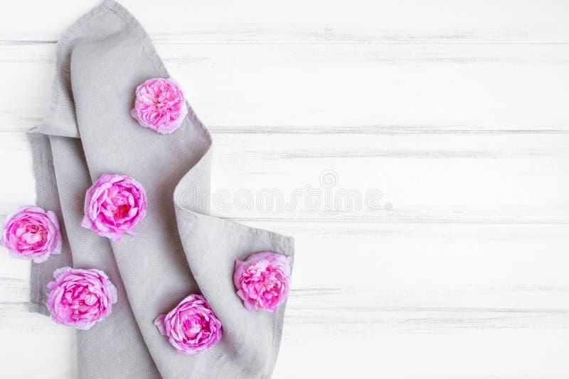 Härliga rosa rosor på grå linnetygbordduk Dekorativ ram på trätabellen för vit tappning Lekmanna- lägenhet, bästa sikt arkivfoto