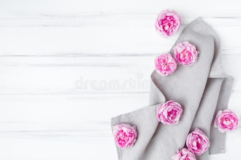 Härliga rosa rosor på grå linnetygbordduk Dekorativ ram på trätabellen för vit tappning Lekmanna- lägenhet, bästa sikt royaltyfri fotografi