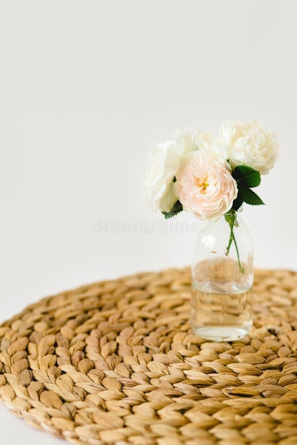 Härliga rosor i exponeringsglasvas på en vide- servett på vit bakgrund arkivbild