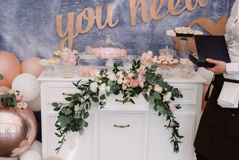 Härliga sötsaker på en skänk Stilfull godisstång på ett modernt bröllop royaltyfri bild