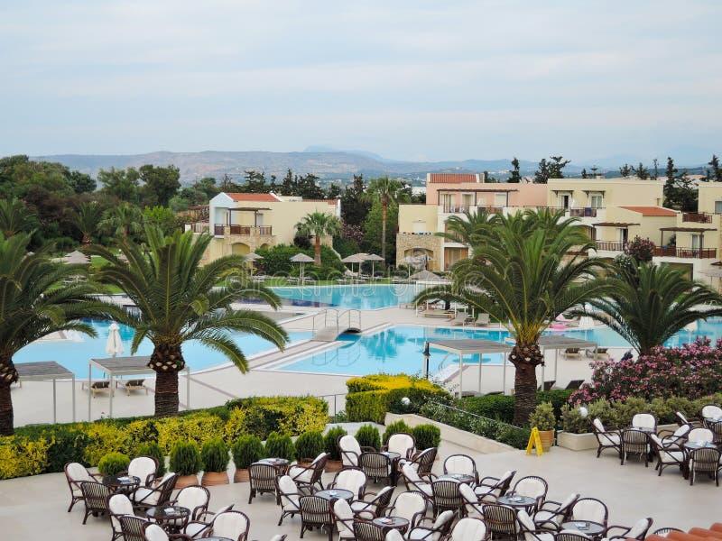 Härliga sikter av hotelljordningen var det finns en utomhus- restaurang och simbassänger pilot- strandsemesterort, crete, Greklan royaltyfri foto