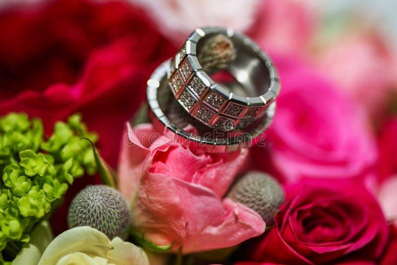 Härliga skinande vigselringar med diamanter på de rosa blommorna royaltyfri bild