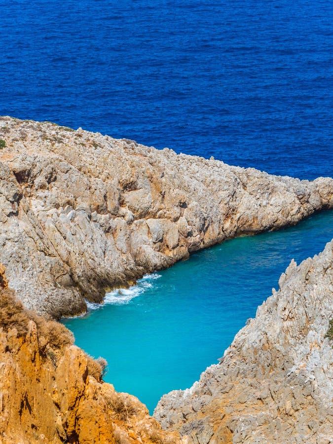 Härliga skuggor av det blåa havet och orange klippor - Grekland arkivfoton