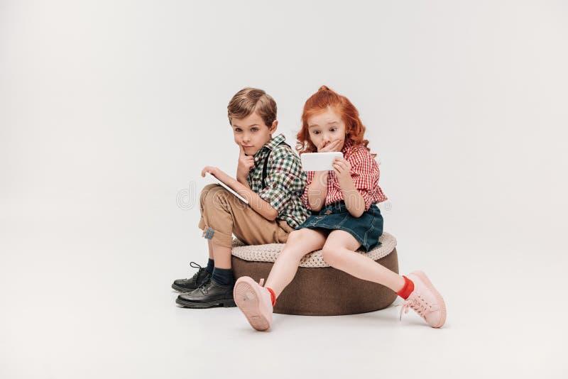 härliga små barn som använder digitala apparater royaltyfria bilder