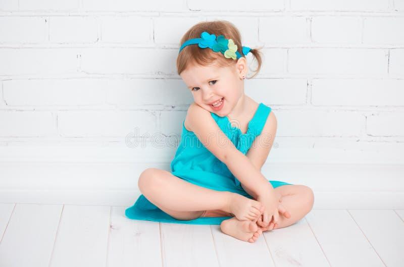 Härliga små behandla som ett barn flickan i en turkosklänning royaltyfri fotografi