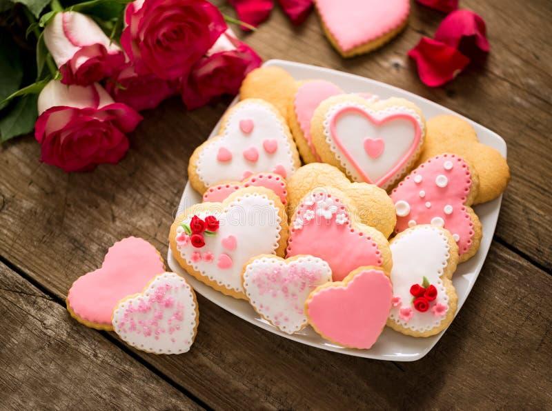 Härliga smakliga valentindagkakor på plattan och rosor arkivbild