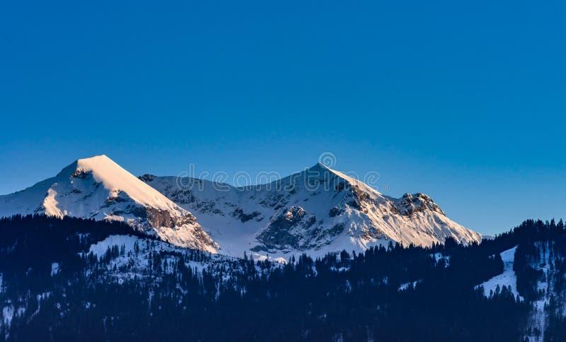 Härliga snöig berg, solig dag i fjällängar royaltyfri fotografi