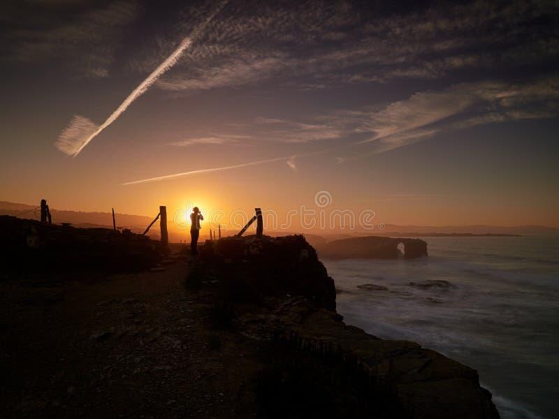 Härliga solnedgång- och stenbågar på Playa de las Catedrales arkivfoto