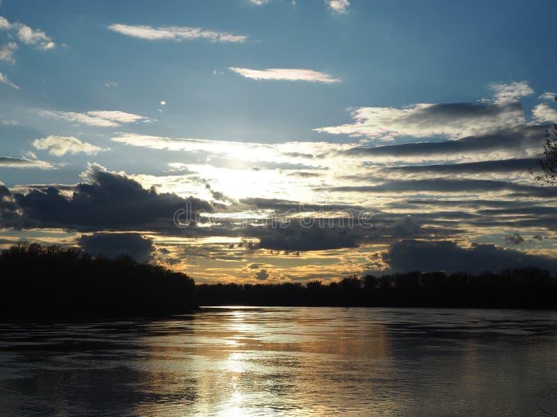 Härliga solnedgångfärger under floden royaltyfri bild