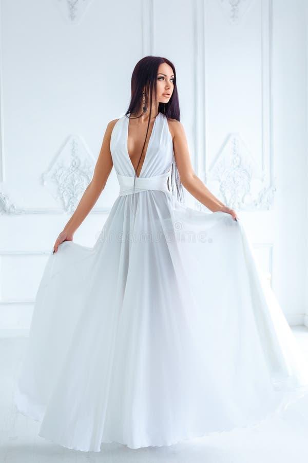 Härliga spensliga brunettställningar i en vit klänning arkivbilder
