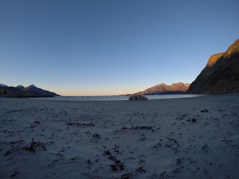 Härliga stillhetblåttvågor som slår den vit fryste sandiga stranden i sen höst i den arktiska cirkeln med det djupa berget och de arkivfoton