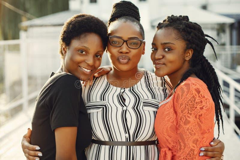 Härliga svarta flickor som står i en sumer, parkerar arkivbild
