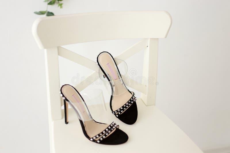härliga svarta heeled sandaler med bergkristaller som står på en vit stol royaltyfri bild