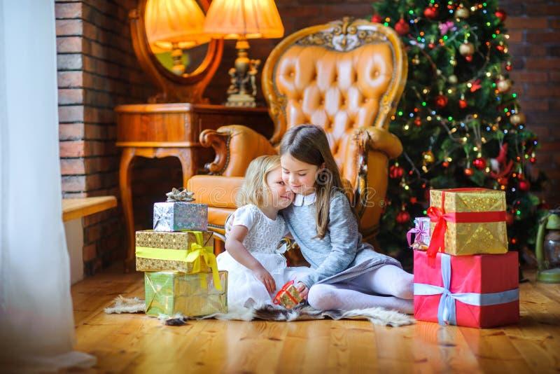 Härliga systrar sitter på golvet nära julgranen royaltyfria foton