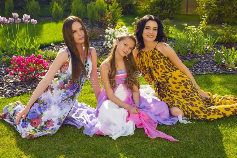Härliga systrar som kopplar av på sommarträdgården arkivbild