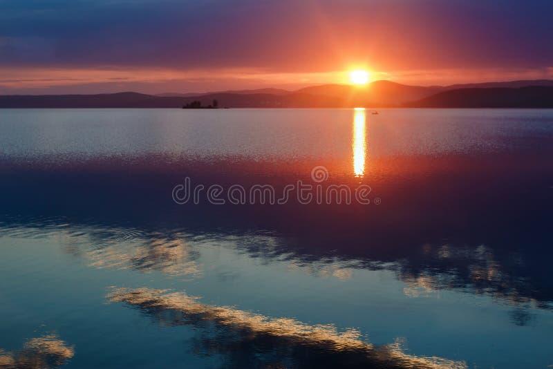 Härliga tidiga rosa färger gryr över en stor sjö, tyst morgon på kusten av en stor sjö fotografering för bildbyråer