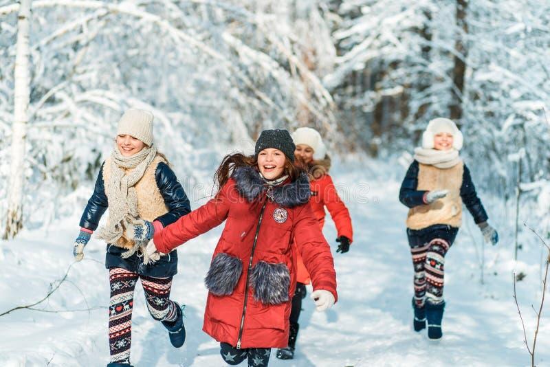 Härliga tonårs- flickor som har den roliga yttersidan i ett trä med insnöad vinter Kamratskap och aktivt livbegrepp royaltyfri bild