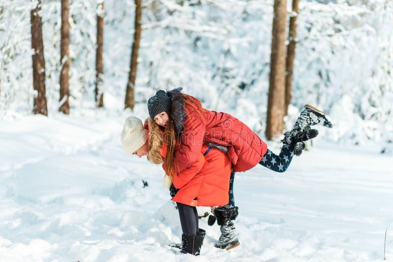 Härliga tonårs- flickor som har den roliga yttersidan i ett trä med insnöad vinter Kamratskap och aktivt livbegrepp royaltyfri fotografi