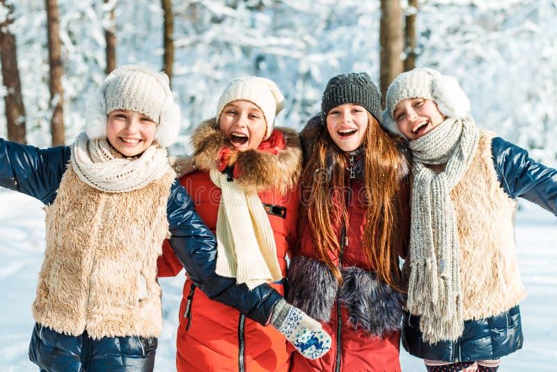 Härliga tonårs- flickor som har den roliga yttersidan i ett trä med insnöad vinter Kamratskap och aktivt livbegrepp royaltyfria foton