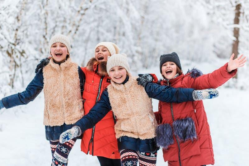 Härliga tonårs- flickor som har den roliga yttersidan i ett trä med insnöad vinter Kamratskap och aktivt livbegrepp arkivfoto