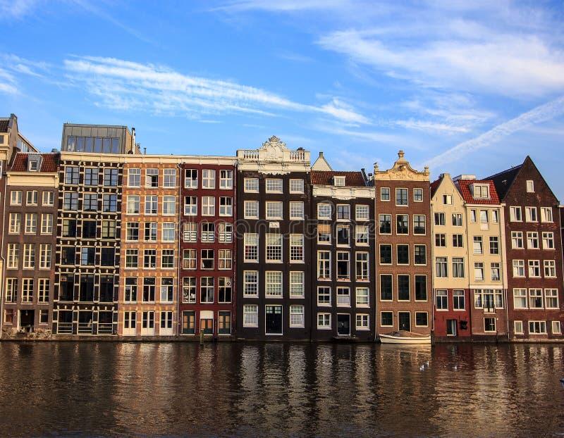 Härliga traditionella gamla byggnader på dagen med ljus blå himmel i Amsterdam, Nederländerna arkivbilder