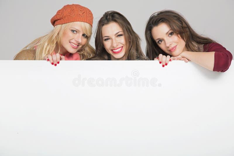 Härliga tre kvinnligvänner med det tomma brädet royaltyfria foton