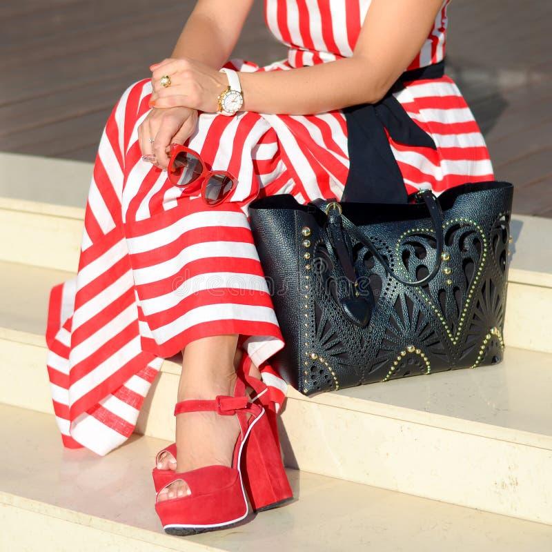 Härliga trendiga skor på kvinna` s lägger benen på ryggen Stilfull damtillbehör röda skor, svart påse, vit sommarklänning eller k royaltyfria foton