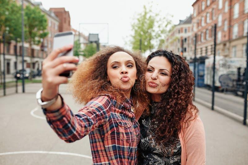 Härliga truta kvinnor som tar en selfie fotografering för bildbyråer