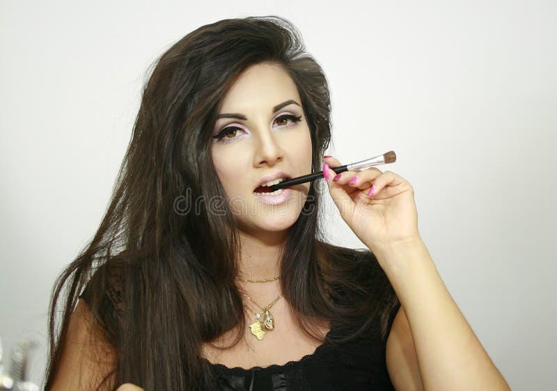 Härliga tuggor för makeupflicka borstar med långt mörkt hår som ser dig skönhet royaltyfri foto