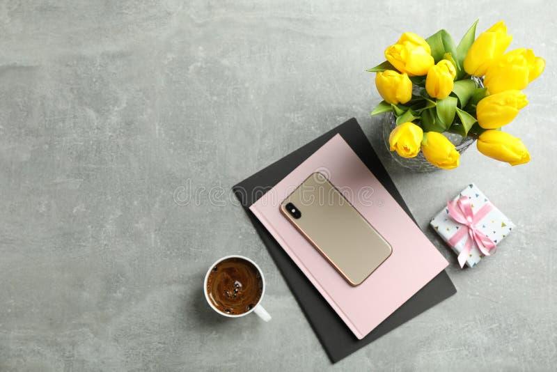 Härliga tulpan i vas och smartphone med tillbehör på grå bakgrund fotografering för bildbyråer