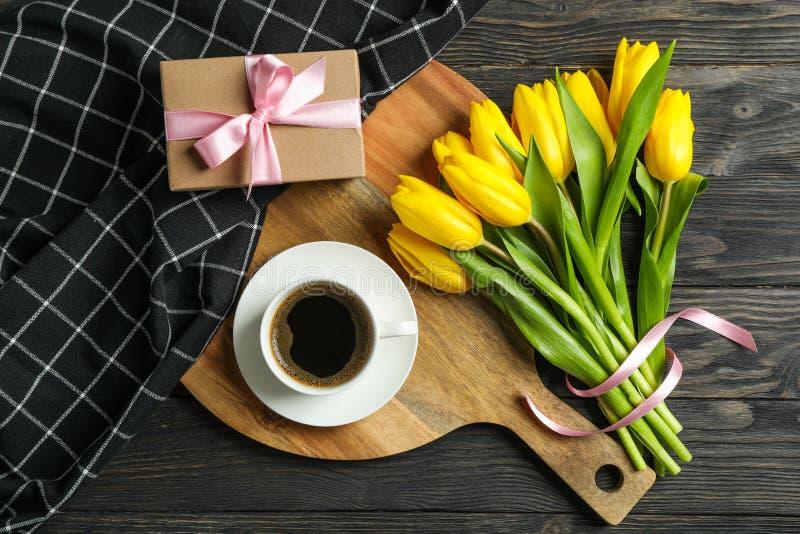 Härliga tulpan, kopp kaffe, gåva och handduk arkivfoto
