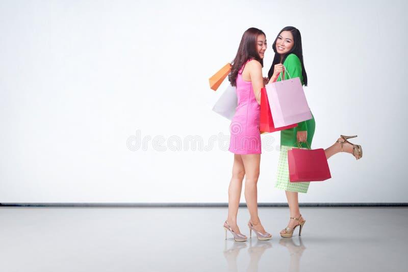 Härliga två asiatiska flickor med färgrika shoppingpåsar arkivbilder
