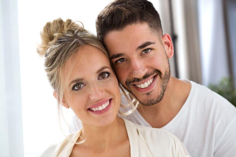 Härliga unga älskvärda par som hemma ser kameran royaltyfri bild